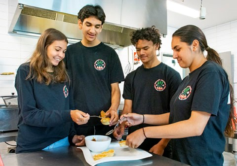 Four students preparing food